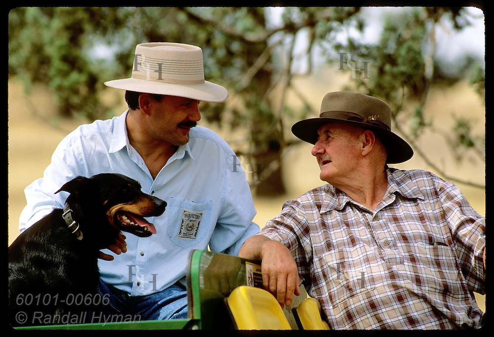 Farmer Jack Veitch turns around to talk to buddy in back of his all-terrain vehicle;Coolamon,NSW Australia