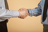Businessmen shaking hands mid section