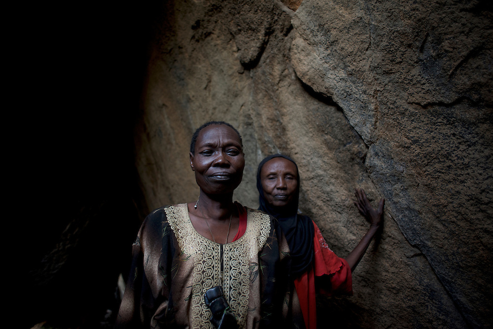 Nuba women take cover from possible bombardments by Sudan's Army Forces airplane in some caves near Buram village.