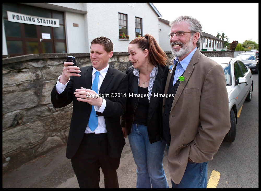 Sinn Fein's Party leader Gerry Adams joins in on a selfie with Matt Carthy, Sinn Fein's Midland & Northwest candidate and voter Lisa McArdle from County Louth outside the Doolargy National School in Ravensdale, County Louth, Ireland,  Friday May 23rd. Polling stations will remain open until 10pm. Almost 2,000 candidates are contesting the 949 local authority seats, while 41 hopefuls are in the race for 11 MEP seats spread over three constituencies while counting has begun in the local elections in Northern Ireland. Over 900 candidates are competing for the 462 seats on 11 new local authorities. Final results are expected to be known by tomorrow afternoon. Counting in the European Elections begins in Belfast on Monday morning. Friday, 23rd May 2014. Picture by  i-Images / i-Images
