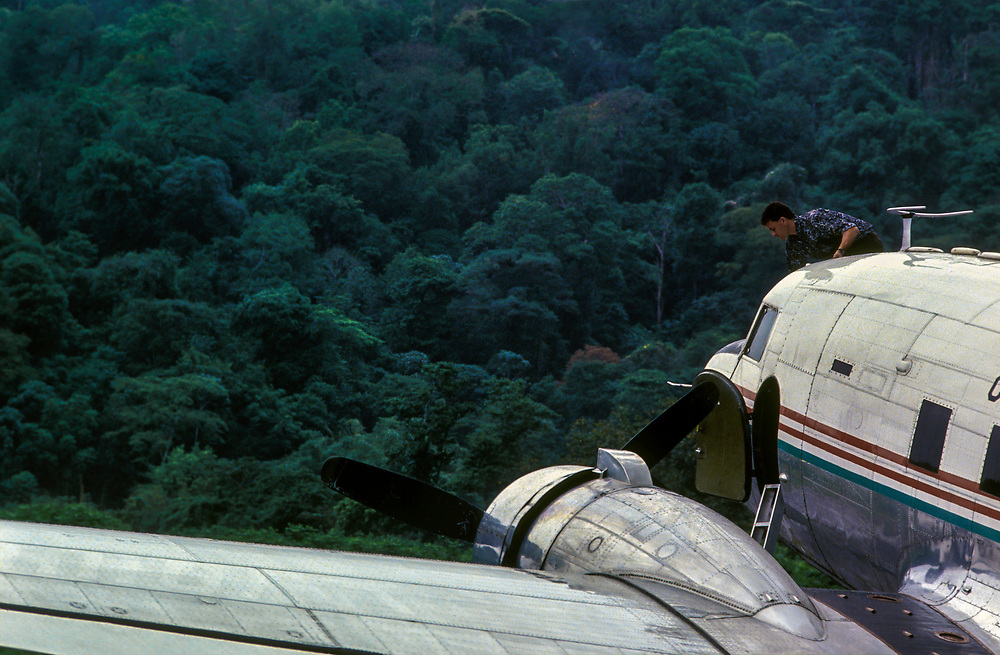 The pilot cleans the windshield of a Dakota DC3 airplane on a landing strip in the Choco rainforest, Colombia