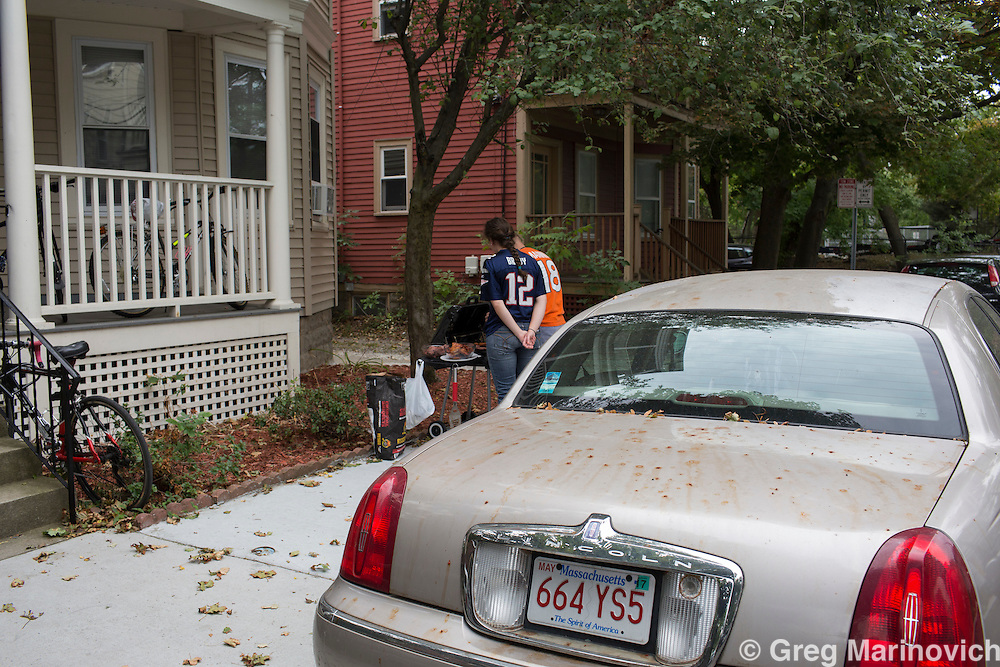 James Green and his girlfriend, a Peace Corps volunteer barbeque for friends on a sidewalk in Cambridge MA as they listen to a football game on the radio. She supports the Patriots and he the Dolphins. Photo Greg marinovich