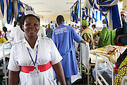 Sister Judith Kyarisiima, the midwife in charge, on the ward at Mbarara Regional Hospital, Uganda.<br /> <br /> The maternity unit is overwhelmingly busy. Hundreds of women accommodate every available area in the four wards. When bed space runs out women who are on their second night in hospital are transferred to mattresses on the floor so that new admissions can take their beds. The department has just twenty midwives to cover the evening, morning and night shifts. Some days there are just two midwives on duty in a postnatal ward that accommodates 70 women and their babies.