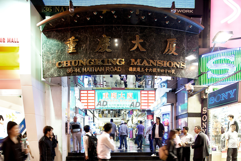 The main gate of Chungking Mansion. *** General Caption *** Chungking Mansions building, located at 36-44 Nathan Road in Tsim Sha Tsui, is supposedly residential, it is made up of a labyrinth of hundreds  low cost guesthouses, curry restaurants, African bistros, clothing shops, sari stores, and foreign exchange offices. It often acts as a large gathering place for some of the ethnic minorities in Hong Kong, particularly South Asians (Indians, Nepalese, Pakistanis, Bangladeshis and Sri Lankans), Middle Eastern people, Nigerians, Europeans, Americans, and many other peoples of the world. Chungking Mansions is 17 stories tall and consists of five blocks, A, B, C, D and E. There are two lifts in each block, one of which serves even-numbered floors, the other one odd-numbered floors. A CCTV camera system exists at the ground floor level for each of the lift cars. The first two floors are however common space where you can wander around under the blocks , the third floor is actually a terrace level between the blocks where the tower blocks rise out of the base of the building and all floors above this are accessible only by the stairways and lifts contained in each block. It is also known to be a centre of drugs, and a refuge for petty criminals, scammers, and illegal immigrants. 208 CCTVs were installed throughout the building in 2004 and under the central control of a security company. It also hires security guards and cleaning workers to patrol in the building day to night and ensure the cleanliness of the building respectively. From time to time, police officers and the immigration officers check the identity of the people inside this building in order to crackdown on drug-trafficking, overstaying and other criminal offences. With all these effort the security and environment in Chungking Mansions has been improving significantly.