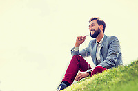 Young attractive businessman talking on smartphone with earphones on while sitting on the grass