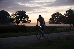 © Licensed to London News Pictures. 26/09/2015. City, UK. A cyclist riding at Sunrise on a misty cold Autumn Morning in Richmond Park, London. Photo credit : Ian Schofield/LNP
