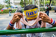 01 DECEMBER 2013 - BANGKOK, THAILAND: A man wipes tear gas out of his eyes during an anti-government riot in Bangkok. Thousands of anti-government Thais confronted riot police at Phanitchayakan Intersection, where Rama V and Phitsanoluk Roads intersect, next to Government House (the office of the Prime Minister). Protestors threw rocks, cherry bombs, small explosives and Molotov cocktails at police who responded with waves of tear gas and chemical dispersal weapons. At least four people were killed at a university in suburban Bangkok when gangs of pro-government and anti-government demonstrators clashed. This is the most serious political violence in Thailand since 2010.    PHOTO BY JACK KURTZ