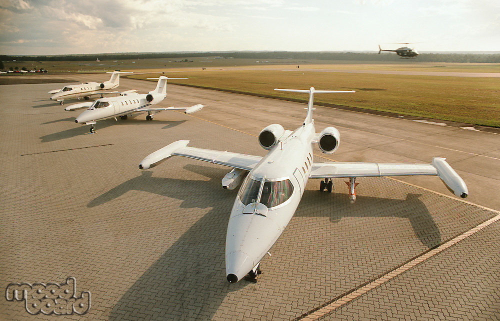 Three jet plains at airport helicopter in background elevated view