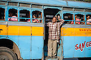 Man traveling at door of blue bus in Kolkata (India)