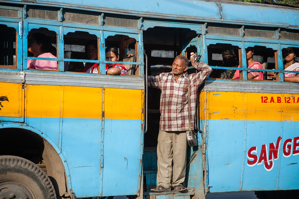 Man traveling at door of blue bus in Kolkata (India)