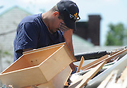 A man wipes his eyes as he sorts through children's clothes on the roof of his home a day after a tornado in Springfield, Mass. Residents of 19 communities in central and western Massachusetts woke to widespread damage Thursday, a day after at least two late-afternoon tornadoes shocked emergency officials with their suddenness and violence and caused the state's first tornado-related deaths in 16 years.  (AP Photo/Jessica Hill)