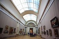Crowds wander through the hallways and admire the paintings in The Louvre Museum, Paris, France.