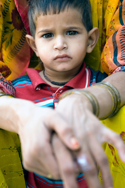 Young boy from Rajasthan, protected by his mother (India)