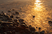 The bright, golden glint of the setting sun stretches across Puget Sound to the rocky beach at Mukilteo, Washington.