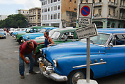 HAVANA, CUBA - OCTOBER 21, 2006: Unidentified people look to the vintage cars parked at the street in Havana, Cuba.