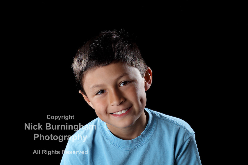 Smiling boy on black background with dramatic side lighting