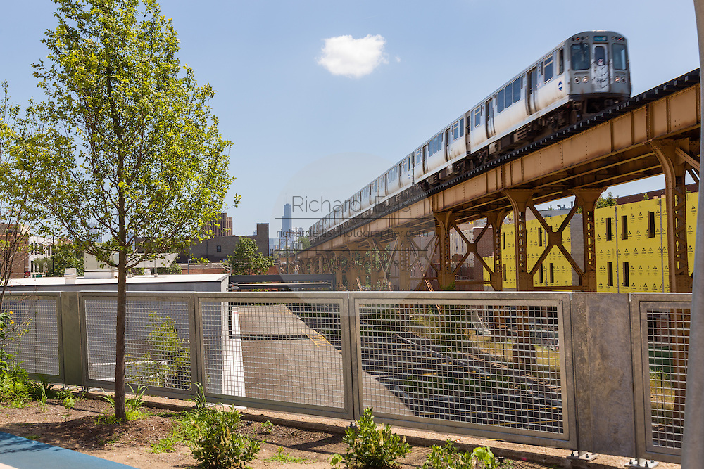 A L train on the Blue Line overpass at Milwaukee Avenue along the 606 elevated bike trail, green space and park built on the old Bloomingdale Line in the Wicker Park neighborhood in Chicago, Illinois, USA