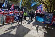 On the day that the EU in Brussels agreed in principle to extend Brexit until 31st January 2020 (aka 'Flextension') and not 31st October 2019, passers-by walk alongside Brexiteer flags and banners during a Brexit protest outside parliament, on 28th October 2019, in Westminster, London, England.