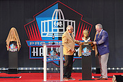 Aug 3, 2019; Canton, OH, USA; Johnny Robinson (left) and presenter Bob Thompson unveil bust of Robinson during the Pro Football Hall of Fame Enshrinement at Tom Benson Hall of Fame Stadium. (Robin Alam/Image of Sport)