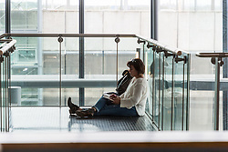 A woman catches up with work on a flight of stairs at Terminal 5 at Heathrow Airport after an IT glitch brings British Airways systems to a halt, causing disruption to thousands of passengers with flights cancelled and delayed. London, August 07 2019.