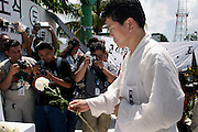 14 SEPTEMBER 2003 - CANCUN, QUINTANA ROO, MEXICO:  Seo Jung-Eui, president of the Korean Advanced Farmer Federation places flowers at an alter for Lee Kyung-hae,  during a memorial service Sunday for the Korean farm activist who publicly committed suicide Wednesday in Cancun to protest World Trade Organization agricultural policies, has been built where he died in a park in Cancun. Thousands of protestors opposed to the World Trade Organization and globalization have come to Cancun to protest the WTO meetings taking place in the hotel zone. Mexican police restricted most of the anti-globalization protestors to downtown Cancun, about five miles from the convention center.  PHOTO BY JACK KURTZ