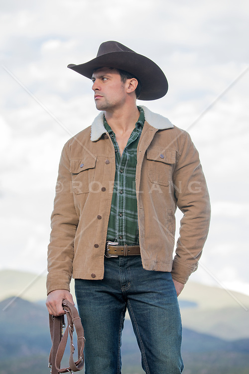 cowboy holding reins outdoors on a ranch