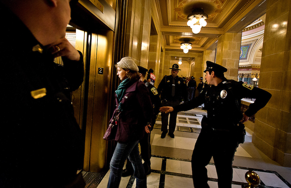 MADISON, WI — FEBRUARY 25: A protestor is escorted down the elevator by Captiol police during protests at the Wisconsin State Captiol over controversial right-to-work legislation.