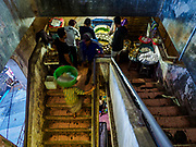 04 AUGUST 2017 - PAYANGAN, BALI, INDONESIA: A vender set up on the stairs in the local market in Payangan, about 45 minutes from Ubud. Bali's local markets are open on an every three day rotating schedule because venders travel from town to town. Before modern refrigeration and convenience stores became common place on Bali, markets were thriving community gatherings. Fewer people shop at markets now as more and more consumers go to convenience stores and more families have refrigerators.      PHOTO BY JACK KURTZ
