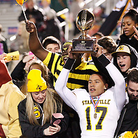 Thomas Wells | Buy at PHOTOS.DJOURNAL.COM<br /> Starkville's Montario Montgomery joins the students with the state championship trophy on Friday after their 27-7 victory over Petal.