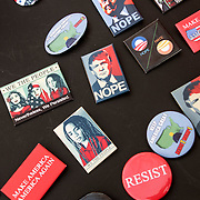 """Humorous political Anti President Trump Buttons:  """"We the People"""", """"Here to Stay"""", """"We Won't Go Back"""", """"I Stand with Refugees"""" and others  for sale at Demonstration Rally in Washington Square Park."""