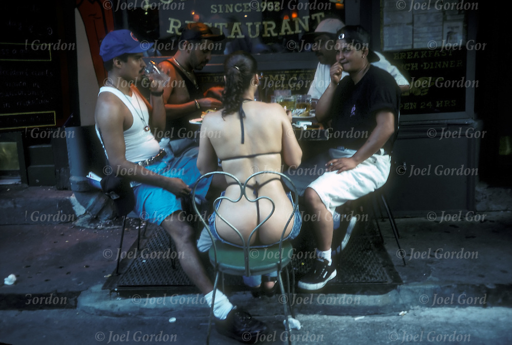 Semi-nude woman sitting in outdoor cafe exhibitionism, voyeurism after the Gay Pride Parade - Stonewall 25 NYC
