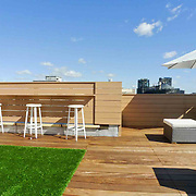 Sunny Modern roofdeck designed for young family with Ipe deck, Synlawn and bar, enclosed in Horizontal fencing.