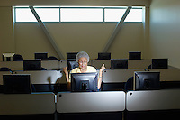 Mature female student working in computer classroom