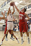 Cedar Rapids Xavier's Andrew Bisenius (34) grabs a rebound over Ottumwa's Brok Hopwood (20) during their game at Xavier High School in Cedar Rapids on December 10, 2013.