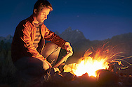 A man sitting outside next to a campfire with the Teton Range and night sky in the background.