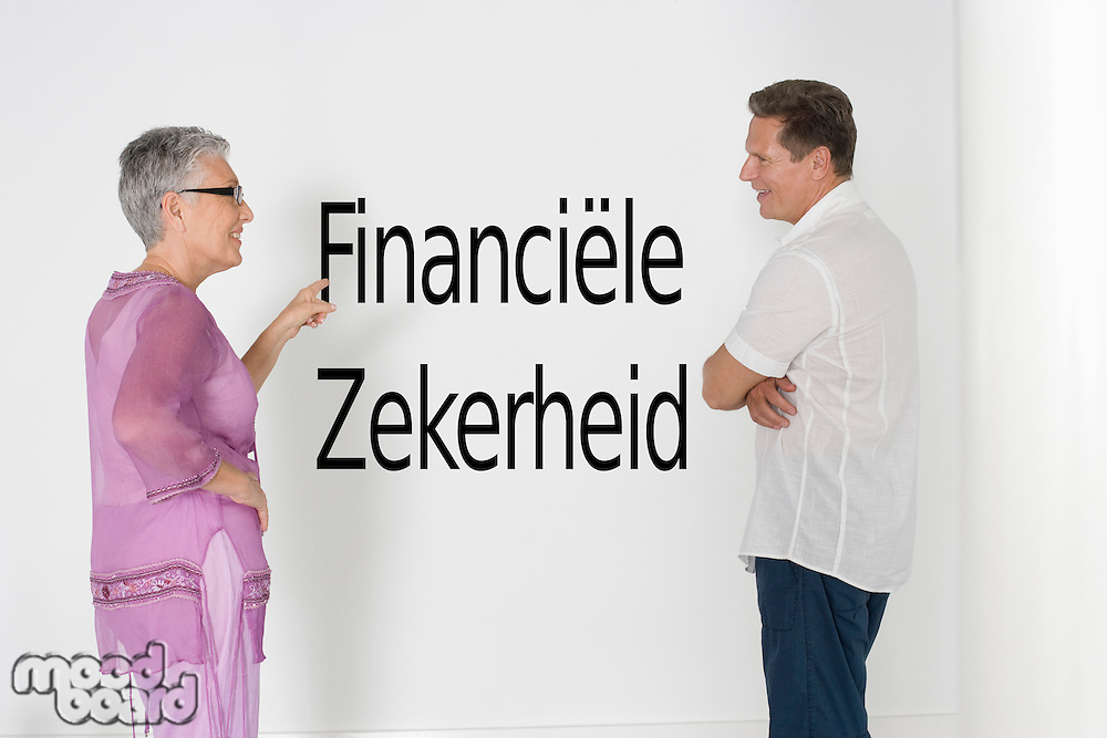 Couple discussing financial security against white wall with Dutch text