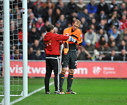 Swansea City's Gerhard Tremmel gets assisted in changing his goal keeping top due to being the same colour as manchester city's away kit.  - Photo mandatory by-line: Alex James/JMP - Tel: Mobile: 07966 386802 01/01/2014 - SPORT - FOOTBALL - Liberty Stadium - Swansea - Swansea City v Manchester City - Barclays Premier League