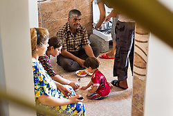 © Licensed to London News Pictures. Hamdaniyah, Iraq. 26/07/2014. Lunch is seen cooking on a gas cooker used by 17 members of an extended family of Iraqi Christian refugees from Mosul in their partially built house in Hamdaniyah, Iraq. The family left Mosul on Friday the 18th of July when Islamic State fighters issued an ultimatum to the city's Christian community. When the family left they were forced to pay a tax for their car, and one son (19) was threatened at knifepoint to ensure they handed over all of their possessions including family photographs.<br /> <br /> Having taken over Mosul Iraq's second largest city in June 2014, fighter of the Islamic State (formerly known as ISIS) have systematically expelled the cities Christian population. Despite having been present in the city for more than 1600 years, Christians in the city were given just days to either convert to Islam, pay a tax for being Christian or leave; many of those that left were also robbed at gunpoint as they passed through Islamic State checkpoints.. Photo credit : Matt Cetti-Roberts/LNP