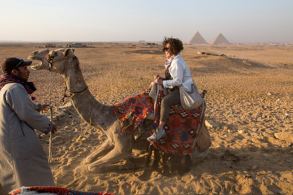 Egypt, Cairo, American tourist Janet Souders on camel safari in Sahara Desert near Great Pyramids of Giza at sunset