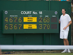 LONDON, ENGLAND - Thursday, June 24, 2010: John Isner (USA) poses next to the scoreboard after the historic longert game ever that lasted 11 hours and five minutes over three days. He beat Nicolas Mahut with the final score of 6-4 3-6 6-7 (7-9) 7-6 (7-3) 70-68 on day four of the Wimbledon Lawn Tennis Championships at the All England Lawn Tennis and Croquet Club. (Pic by David Rawcliffe/Propaganda)