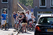 In Utrecht moet een automobilist  zich langs een groep fietsers wringen die de fietsroute van Colorbike Tours aan het doen zijn.<br /> <br /> In Utrecht a car driver has to manouvre his car past a group cyclists who are riding the city tour by Colorbike Tours.