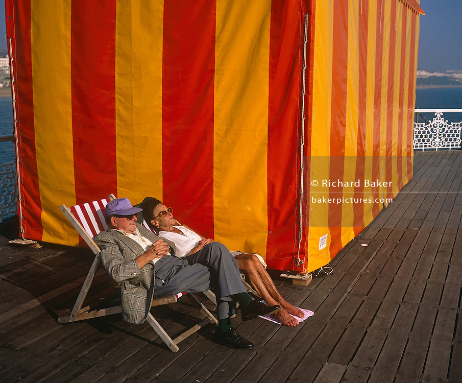 In the shelter of a large red and yellow-striped marquee tent, a middle-aged husband and wife relax in deck chairs on Brighton's East Pier, England. The wife appears to be asleep and has taken the prrecution against splinters from the pier's planks by spreading a tiny towell to rest her feet upon. She has dyed hair and large sun glasses and her bony legs are tanned and veined from much exposure to the sun. The husband is also fully-clothed with a loud checked jacket, black shoes and socks and he sits crossed-legged with a peaked cap and dark glasses with his hands across his belly. They are in a peaceful spot on this pier, a Victorian seaside structure built in 1899 for those taking the air to walk out onto the sea without getting their feet wet.