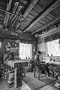 Veteran climber, guide and writer Doug Robinson (age 71) writing in his cabin in Rock Creek Canyon.