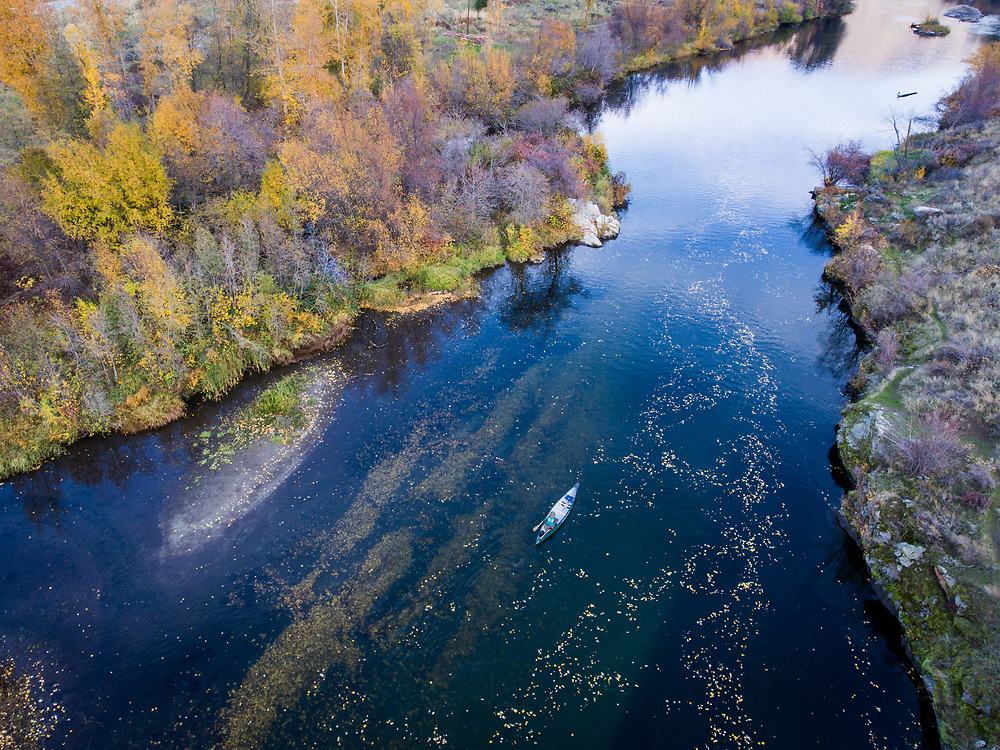 Aerial photo Alan Schmidt paddling a canoe on the mouth of the Entiat River with drifting leaves and fall colors.