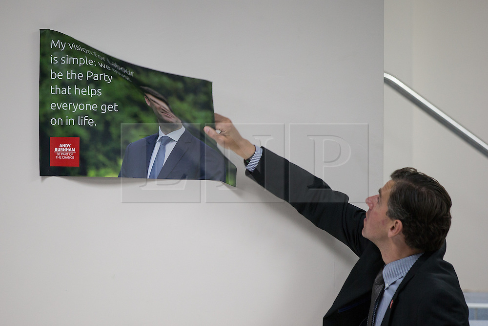 © Licensed to London News Pictures  . 05/09/2015 . Manchester , UK . A man removes posters after a rally Andy Burnham's rally to be leader of the Labour Party , at Kings House Conference Centre in Manchester . Photo credit: Joel Goodman/LNP