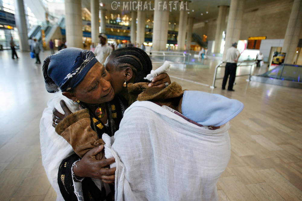Newly arrived Ethiopian immigrants embrace excitement with at a reunion with a family member at the Ben Gurion international airport in Israel, June 2008.