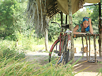 Young woman reading in hut bicycle leaning on pale