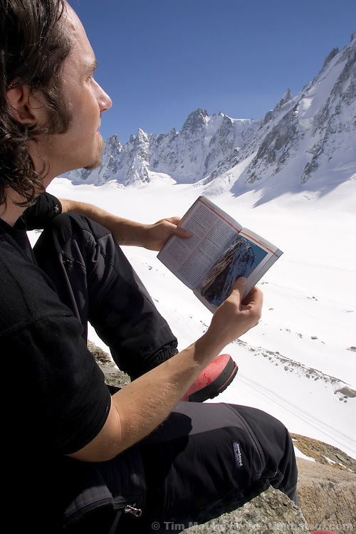 Studying a climbing guidebook at the Argentiere Hut, Argentiere Glacier, Chamonix, France.