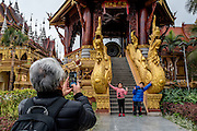 Tourists take photos at a Buddhist temple in Xishuangbanna, China.