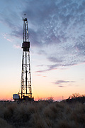 A drilling rig south of Crescent at sunset